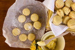 Melting Moments. Delicious oven fresh baked melting moments shortbread biscuits with sweet filling and daisies in a rustic setting Royalty Free Stock Photo