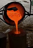Melting pot with liquid bronze. Red hot liquid bronze is poured out Stock Image