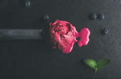 Melting scoop of blueberry ice-cream over black slate stone background Royalty Free Stock Photography