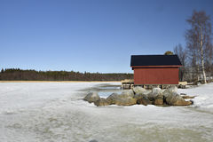 Melting sea ice in spring sun and rocks and a red  boathouse Stock Photography