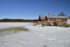 Melting sea ice in spring sun and rocks and three red boathouse Royalty Free Stock Photo