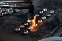 Melting silver in craft jewelry making. Handmade silverware process stock photography