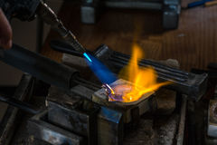 Melting a Silver Ingot in crucible with blowtorch; Royalty Free Stock Photos