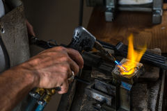 Melting a Silver Ingot in crucible with blowtorch;. Melting a Silver Ingot to liquid state in crucible with blowtorch; Goldsmith Workshop; Close-up stock photos