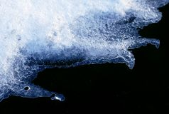 Melting snow and black ground. Ice pieces of frozen blue water in winter Stock Image