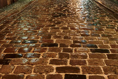 Melting snow on the cobbled street at night Stock Photos