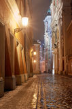 Melting snow on the cobbled street at night Stock Images