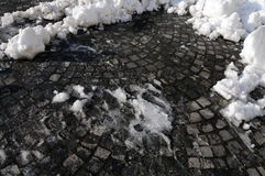 Melting snow on pavement. Snow melting on a sunny day at the end of winter Stock Images