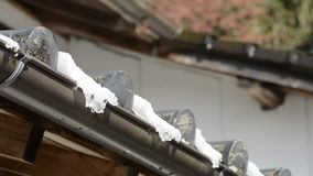 Melting snow on tiled roof stock video footage