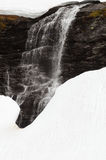 Melting snow waterfall. A view of a cascading waterfall surrounded by drifts of deep, melting snow Royalty Free Stock Image