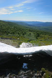 Melting snowfield against the green hills. Royalty Free Stock Photos