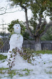 Melting snowman in garden. Decorated with tree branches Royalty Free Stock Photo