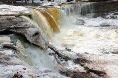 Melting waterfall in Estonia. A photo of a large waterfall partly covered with melting ice blocks ans snow. Some of the ice blocks are dirty. The picture is Royalty Free Stock Photos
