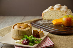Melton Mowbray pork pie ploughman's lunch. An English artisan Melton Mowbray pork pie, wrapped with brown paper and twine next to salad leaves, with boule bread Stock Image