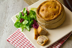 Melton Mowbray pork pies on plate. A large artisan Melton Mowbray pork pie wrapped in brown paper and twine, with small pork pies cut and bitten in front. Salad Royalty Free Stock Photo