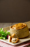 Melton Mowbray pork pies vertical. A large artisan Melton Mowbray pork pie wrapped in brown paper and twine, with small pork pies cut and bitten in front. Salad Royalty Free Stock Photography