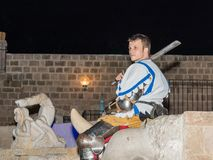 Member of the Knights of Jerusalem club dressed in the traditional armor of a knight, posing for photographers at night in the old royalty free stock images