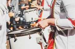 Member of a military fanfare playing a mobile bass drum on a par. Member of a military fanfare playing a mobile bass drum. Playing a mobile bass drum with stock image