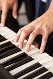 Member's Hands Playing Piano In Recording Studio. Closeup of male band member's hands playing piano in recording studio Stock Photo