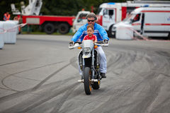 Member from stuntmen team rides motorcycle with child Royalty Free Stock Images