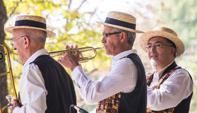 Members of a brass band perform in Luxembourg Garden, Paris. Three straw-hatted members of a brass band perform in the Jardin de Luxembourg, Paris royalty free stock photos