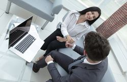 Members of the business team show their success sitting at the desk. Royalty Free Stock Photo