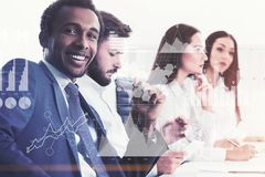 Diverse business team members in office, stats. Members of a diverse business team sitting together at an office table. African American men is looking at the Royalty Free Stock Photography