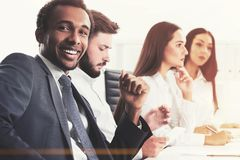 Diverse business team members in office. Members of a diverse business team are sitting together at an office table. African American men is looking at the Royalty Free Stock Image