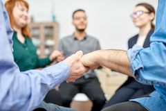Members of Group Therapy Session. Close-up shot of male and female patients with closed eyes sitting in circle and holding hands while participating in group royalty free stock photography