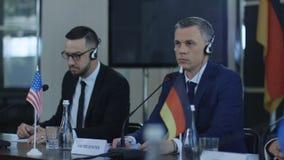 Members of international summit in headphones stock footage