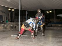 Members of the Knights of Jerusalem club dressed in the traditional armor of a knight, are fighting on swords at night in the old royalty free stock image