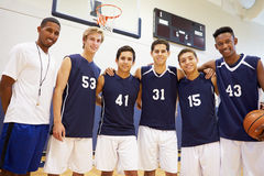 Members Of Male High School Basketball Team With Coach. Looking At Camera Smiling Royalty Free Stock Images
