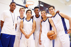 Members Of Male High School Basketball Team With Coach. Looking To Camera Smiling Stock Photo