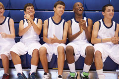 Members Of Male High School Basketball Team Watching Match. Sitting On Bench Cheering Stock Image