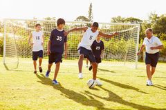 Members Of Male High School Soccer Playing Match. Outside Kicking Ball Stock Photography