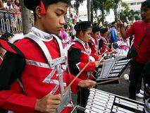 Members of a marching band play their instruments at a parade during the Sumaka Festival in Antipolo City. ANTIPOLO CITY, PHILIPPINES - MAY 1, 2017: Members of stock images