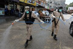 Members of the Palestinian Islamic Jihad`s armed wing, the Al-Quds Brigades, spray disinfectant in the streets of Rafah in the sou