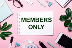 MEMBERS ONLY is written in a white notebook on a pink background surrounded by business accessories and green leaves