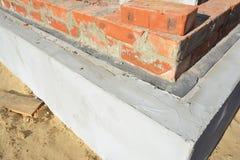 Membrana della prova umida sopra le pareti del fondamento Membrana impermeabile del bitume per la costruzione del fondamento dell fotografia stock libera da diritti