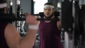 Membre de centre de fitness faisant des postures accroupies avec le barbell, satisfait de son progrès clips vidéos
