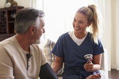 Membre du personnel soignant féminin faisant la visite à la maison à un homme supérieur, prenant sa tension artérielle, fin photographie stock libre de droits