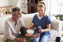 Membre du personnel soignant féminin faisant la visite à la maison à un homme supérieur prenant la tension artérielle images stock