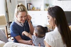Membre du personnel soignant féminin rendant visite à la jeune maman et à son fils nourrisson à la maison, utilisant le stéthosco images stock