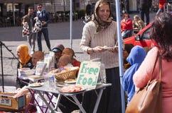 Membre féminin de Krishna de lièvres offrant la nourriture libre dans la rue tandis que d'autres membres payent et chantent image stock