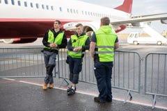 Membres d'équipage se tenant prêt la barrière Against Airplane images stock
