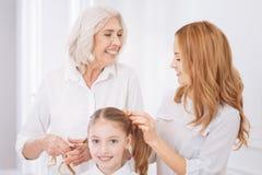 Membres de la famille de Cheerul mettant des cheveux de fille dans une tresse Images stock