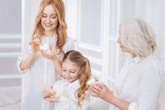 Membres de la famille de sourire joyeux employant des cosmétiques Photo stock