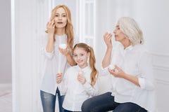 Membres de la famille féminins positifs employant des cosmétiques Image stock
