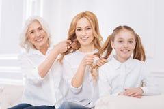 Membres de la famille faisant des coiffures l'un pour l'autre Images stock