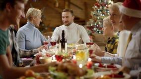 Membres de la famille heureux parlant pendant le dîner de Noël banque de vidéos